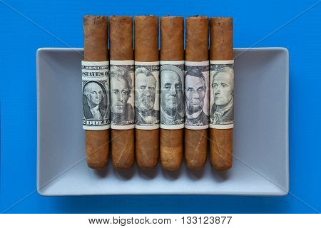 Gray ceramic dish and luxury Cuban cigars with US dollar banknotes on over blue background rectangle dish