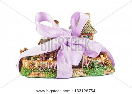 Toy house with bow as gift isolated on white background