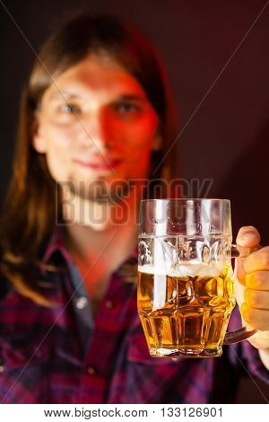 handsome young man guy holding a glass mug of beer