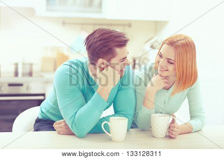 Happy young couple drinking tea in the kitchen at home
