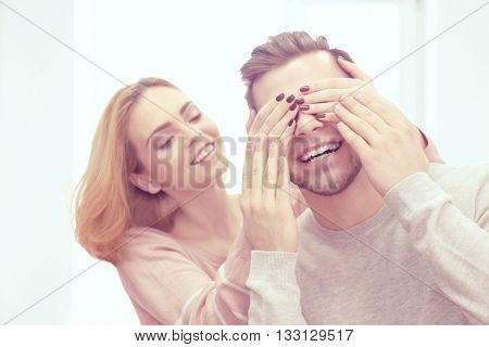 Young woman closing her boyfriend's eyes beside the window