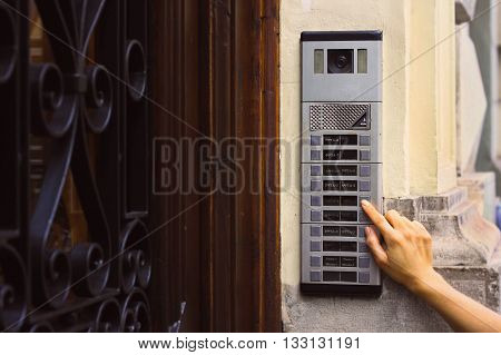 The girl is pressing by finger on the intercom's button with a camera near a beautiful old wooden door
