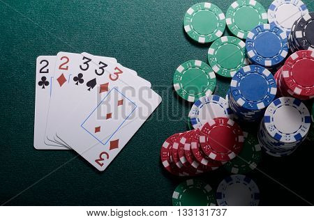 Casino chips and full house cards combination on the green table