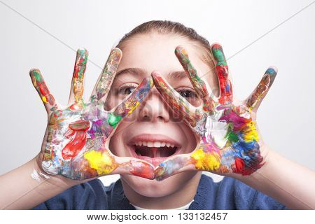 Little student girl showing painted hands on grey background