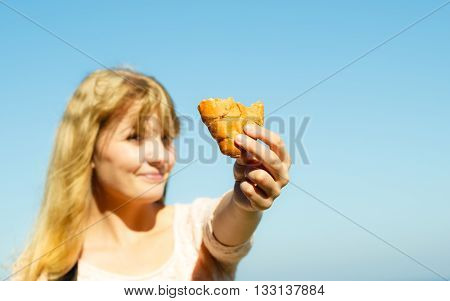 Young woman eating croissant meal food outdoor. Pretty girl having breakfast. Summer pleasure.