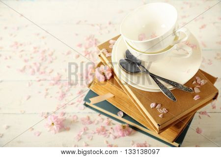 Porcelain cups with books and flowers on table