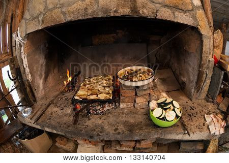 Rustic dinner in the Rhodope mountains - roasting on coals on the grill in the oven just collected delicious porcini mushrooms and chopped vegetables (Rhodopes Bulgaria)