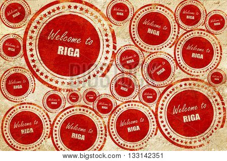 Welcome to riga, red stamp on a grunge paper texture