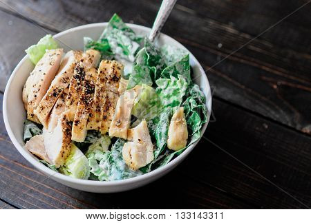 Chicken caesar salad in white bowl on wooden table