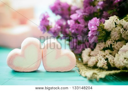 heart shape of marshmallows with statice flower on wood background for love and valentine day vintage toning