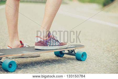 Close-up image of male legs on longboard on road in summer