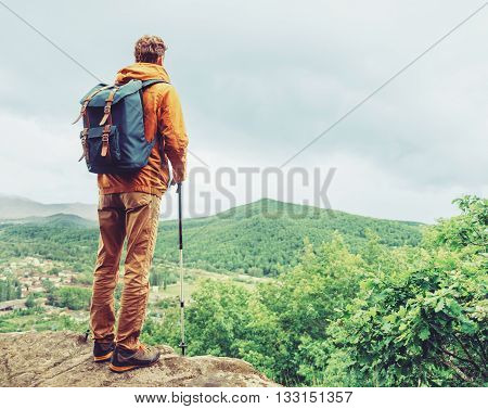 Hiker young man with backpack and trekking poles standing on edge of cliff and looking at the mountains in summer outdoor rear view