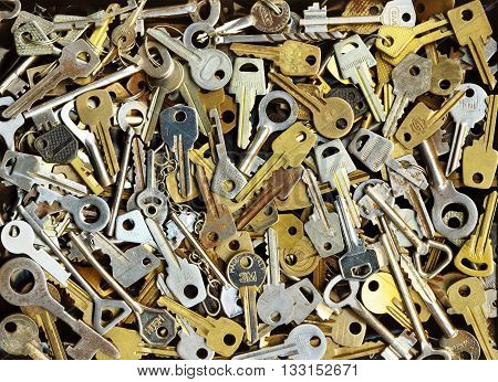 Pile of many different yellow and white old metal keys choice to open a door. Vintage close-up background