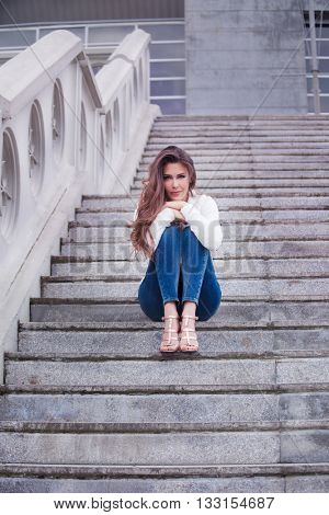 young smiling woman sit on stairs in the city full body shot
