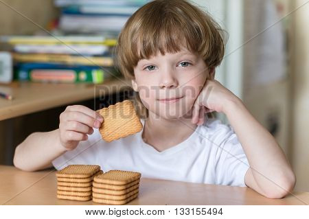 child in the kitchen sitting at the table and eating cookies in the shape of a rectangle.