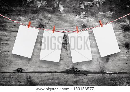 Blank paper or photo frames hanging on the red striped clothesline . On wooden background. Template for your text