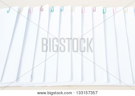 Colorful paper clip with pile of overload white paperwork and reports arranged on wood table.