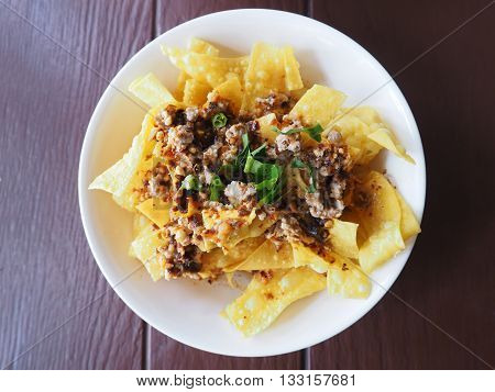 Bowl of fried crispy wonton spicy salad on wooden table