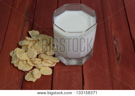 Cornflakes and milk in a glass. Wooden table