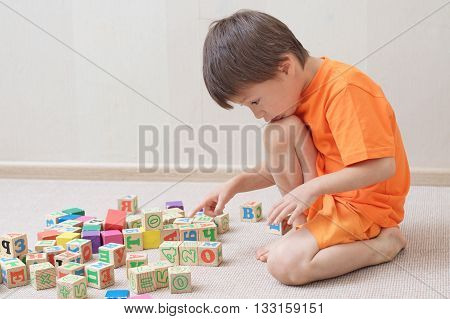 Boy child playing with toy cubes in the room