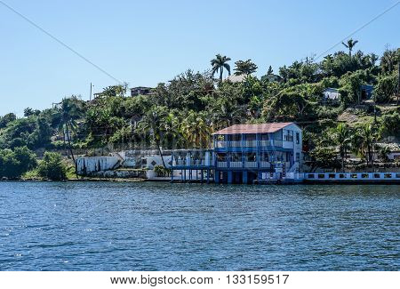 lake views with boathouse in tropical landscape with green hills