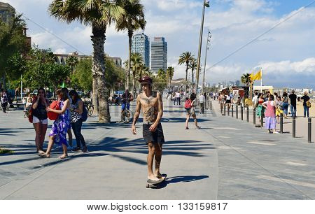 BARCELONA, SPAIN - MAY 30: People walking and skatebording in the seafront of La Barceloneta on May 30, 2016 in Barcelona, Spain. The city has a long and busy seafront