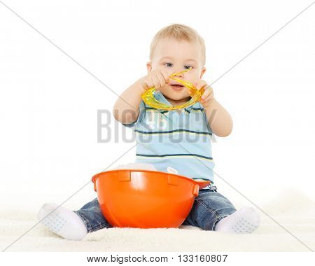 Little child plays with orange construction protective helmet and huge yellow protective eyeglasses on a white background. Profession - future builder.