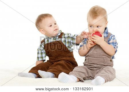 Two little boys with fresh apple sit on a white background. Healthy food.