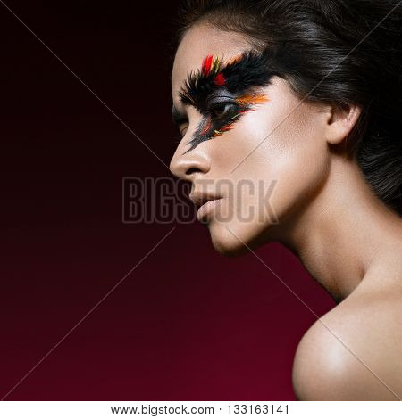 Beautiful girl in the image of the Phoenix bird with creative makeup .The beauty of the face. Photos shot in studio