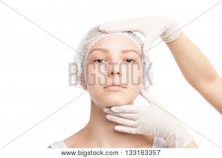 Portrait of young woman in medical hat looking at camera while doctor touches her face. Isolated
