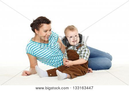 Young mother with sweet child play on a white background. Happy family.