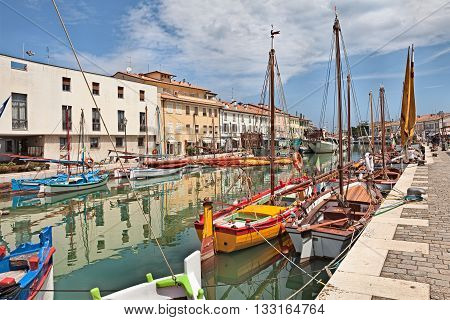 CESENATICO (FC) ITALY - JUNE 4: the port canal designed by Leonardo da Vinci in the old town with colored wooden sailboats on January 12 2013 in Cesenatico Emilia Romagna Italy