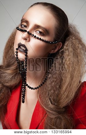 Concept shot of fair-haired woman with black beads on face looking at camera