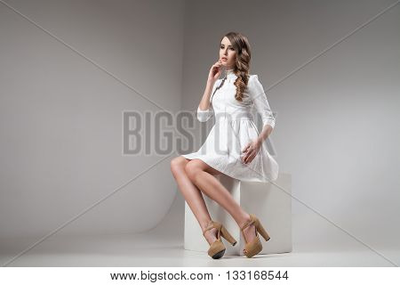 Brunette in white dress looking away while sitting in studio against of white background