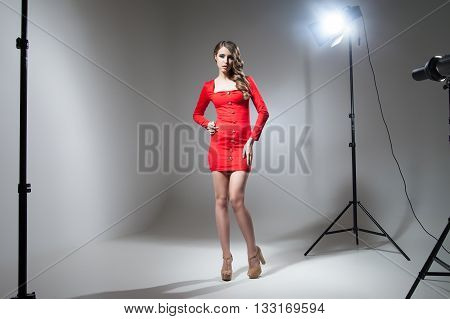 Seductive model in red dress in spotlight. Studio shot
