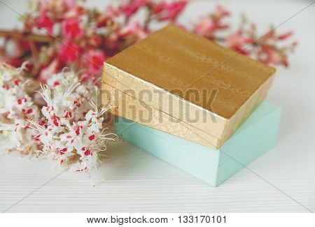 There Gold and Blue Boxes with White and Pink Branches of Chestnut Tree are on White Table,Selective Focus