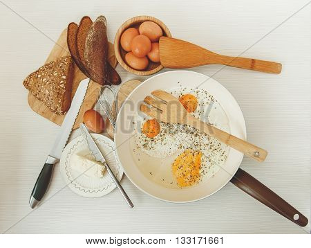 Fried Eggs in the Frying Pan,Breakfast Ingredients.Bread,Butter.Kitchen Accessories.Cooking Morning Food.White Table.Top View