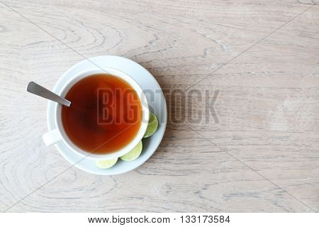 Cup of ginger lemon tea on the wooden table