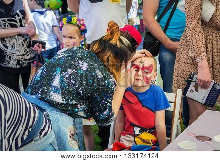 Zaporizhia/Ukraine- June 5, 2016: volunteer  painting mask on a boy`s face during charity family festival organized in regions with most quantity of refugees from Donetsk area, occasioned with International Children`s Day