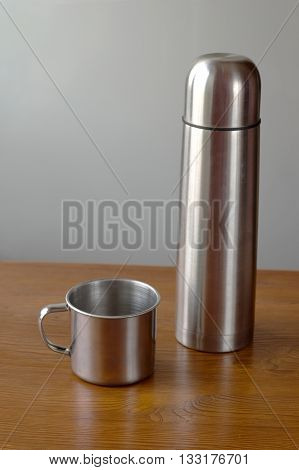 thermos mug with iron on a wooden background