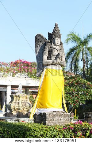 Huge Bali stone sculpture wrapped in yellow fabric