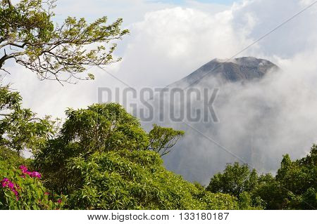 The perfect peak of the active and young Izalco volcano seen from a view point in Cerro Verde National Park in El Salvador, covered with thick white clouds