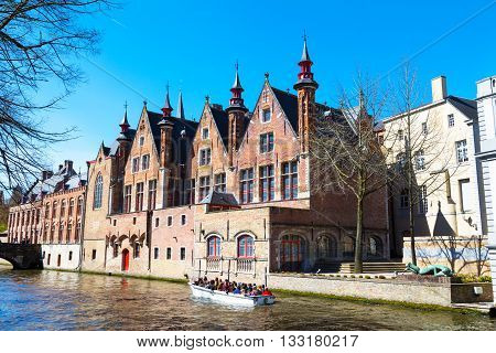 Bruges, Belgium - April 10, 2016: Scenic cityscape with medeivel houses, boat with tourists at Green canal, Groenerei in Bruges, Belgium
