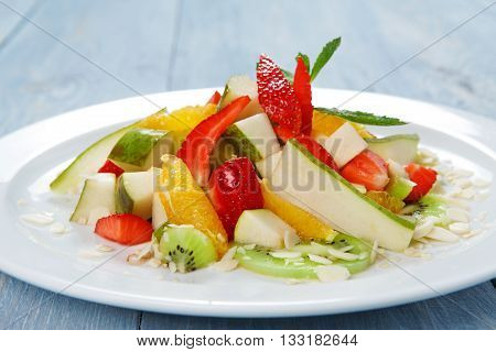 Healthy dessert. Sweet fruit salad closeup. Vegetarian diet. Fruit salad at white plate. Healthy diet food, natural organic vegan salad with pear, strawberry, orange and almond slices.