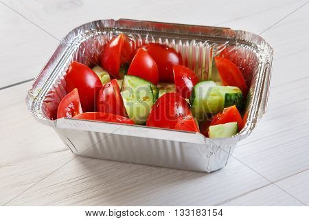 Healthy lunch. Dieting food, Take away organic food. Weight loss diet, take away in aluminium box. Healthy food. Vegetable salad from tomatoes and cucumbers at white wood, closeup