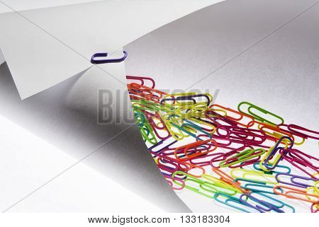 Colorful paperclips on a folded white paper