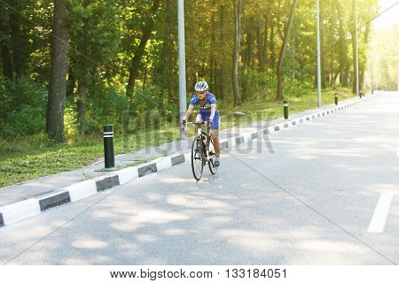 Cycling on the road. Woman cycling on countryside summer road or highway. Female training for triathlon or cycling competition. Highway cycling