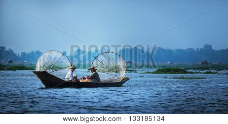 Mandalay - October 15: Fishermen catch fish Oct 15 2014 in Mandalay. Fishermen show ancient way of fishing nets