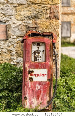 Old gas pump outside an old house