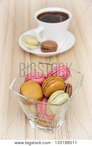 French colorful macarons with cup of black coffee. Sweet delight. Food and drink. Vertical composition. Food theme. Tasty macarons.